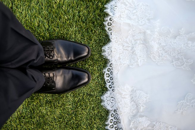 Looking down at a bride and grooms shoes | Kelly Chandler Consulting