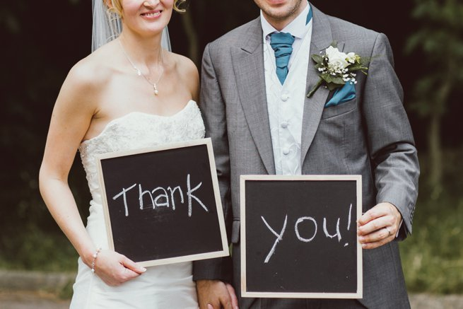 Bride and groom holding thank you chalk board signs | Kelly Chandler Consulting