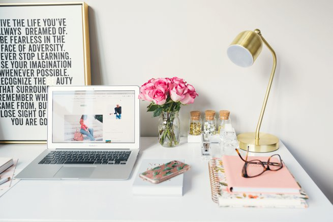 Styled desk with laptop roses in a vase and stacked books with glasses on top | Kelly Chandler Consulting